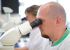 Man in lab kijkend door apparatuur